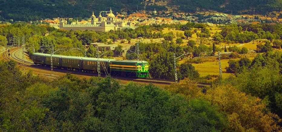 Tren Turístico de Felipe II, con el municipio de El Escorial al fondo