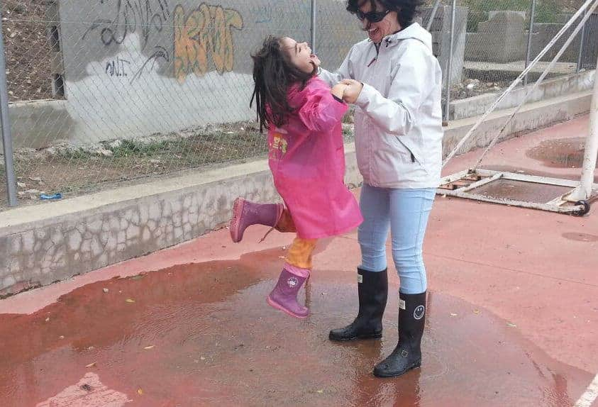 Mamá y la peque saltando charcos