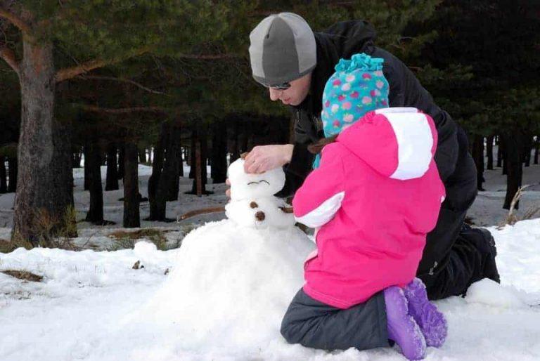La peque con papá haciendo un muñeco de nieve