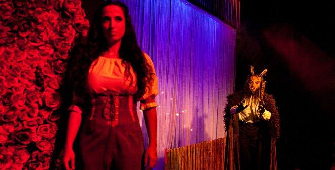 Personaje de Bella con Bastian, la Bestia al fondo del escenario, en La Bella y la Bestia el musical, de Mundiartistas