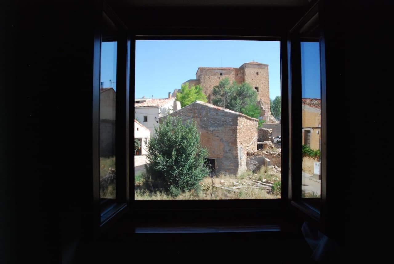 Ventana desde La Ínsula de Castilnuevo, donde se ve un edificio antiguo del pueblo