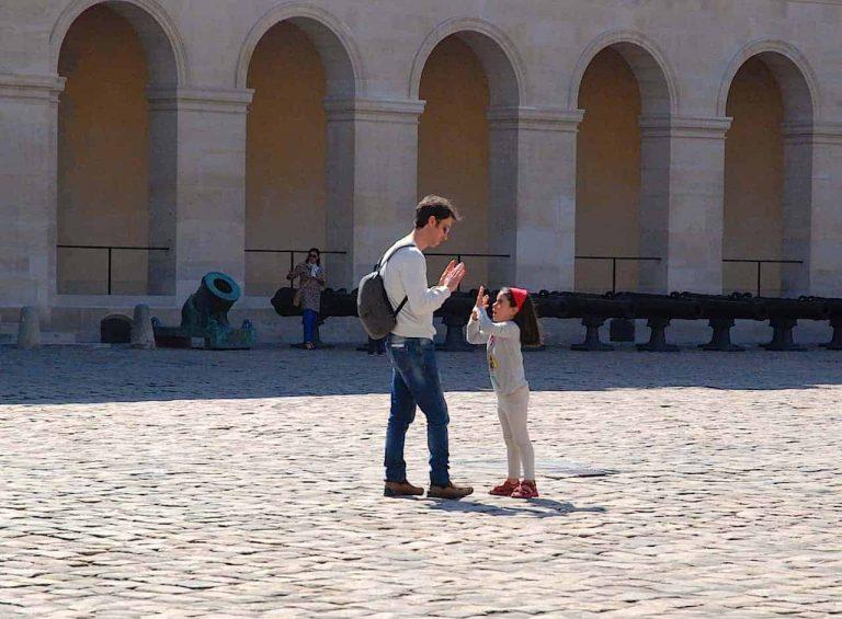 La peque y el papá juegan a un juego de palmas en el patio de Les Invalides, en Paris