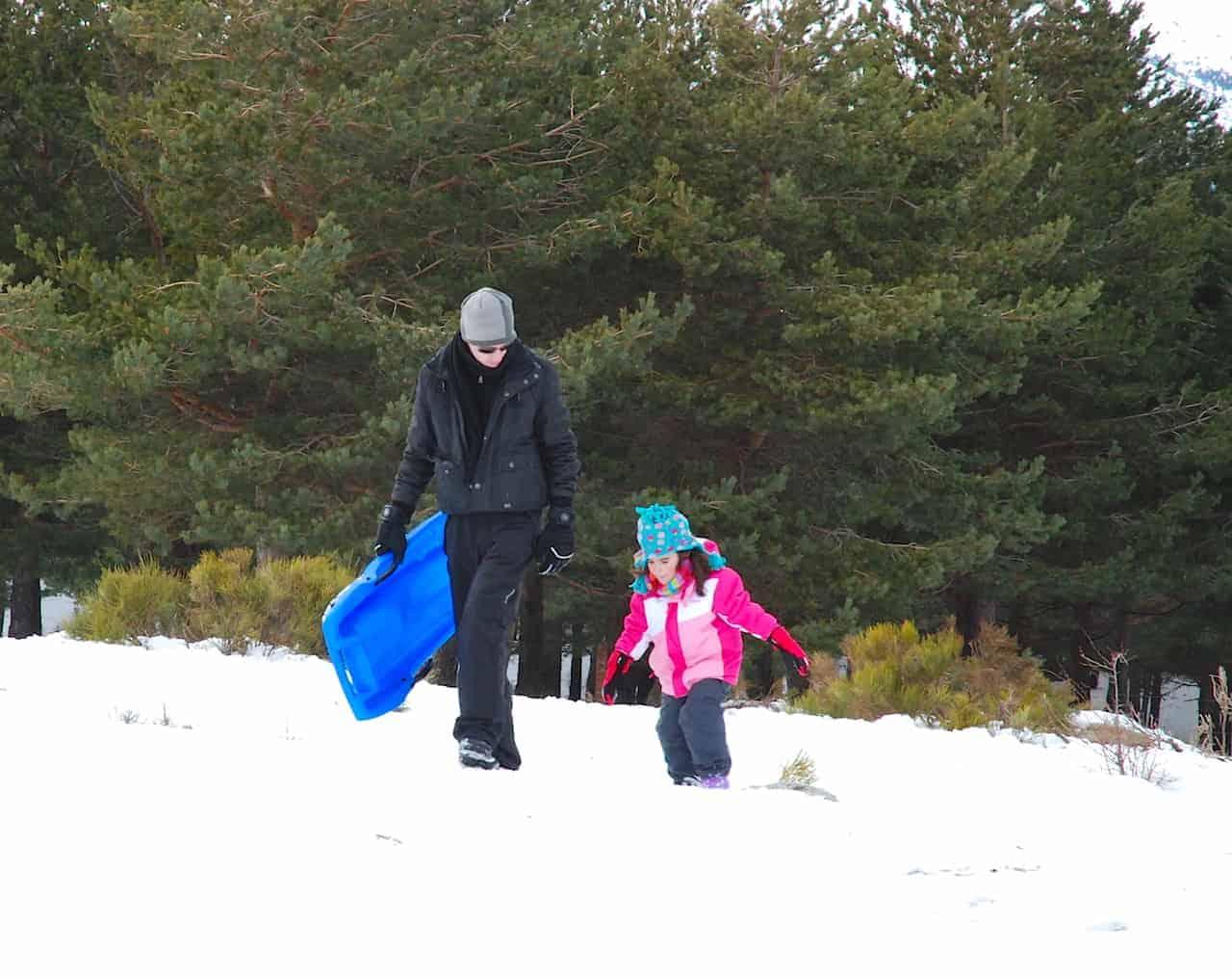 Papá y la peque andando por la nieve con el trineo en la mano