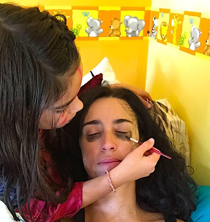 Niña maquillando a su madre para la fiesta de halloween